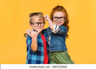 portrait of smiling kids in eyeglasses isolated on yellow