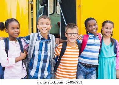 Portrait of smiling kids standing with arm around in front of school bus