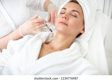 Portrait of smiling lady lying on bed while getting beauty injection in neck