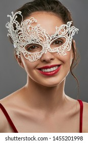 Portrait of smiling lady with tied back brunette hair, wearing wine red crop top. The girl is looking at camera, wearing asymmetric snowy carnival mask with perforation, posing on gray background.