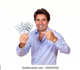Portrait of a smiling latin man holding and pointing cash dollars on white background