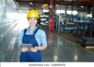 Portrait of smiling Latin-American woman wearing hardhat smiling cheerfully looking at camera while enjoying work in modern factory, copy space