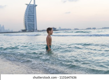 Portrait smiling little baby boy playing in the sea, ocean. Positive human emotions, feelings, joy. Funny cute child making vacations and enjoying summer. Sunset Dubai beach.