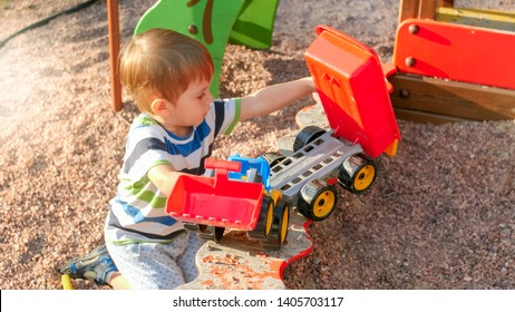 Portrait of smiling little boy sitting in sandpit at playground and digging sand with plastic spade and pouring it in colorful toy truck with trailer