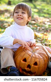 Portrait of a smiling little boy who sitting on the ground in the woods with halloween pumpkin