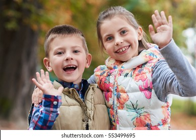 Portrait of a smiling little brother and sister waving hello while enjoying a day outside together in a park in the autumn