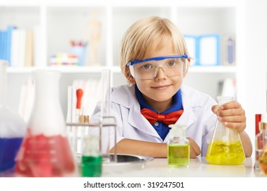 Portrait of smiling little chemist at the table with reagents