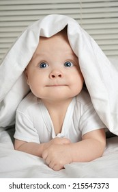 Portrait of smiling little child lying in his crib
