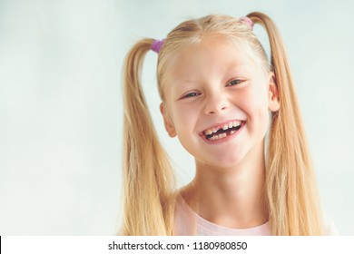 Portrait of a smiling little girl after dropping her front baby tooth