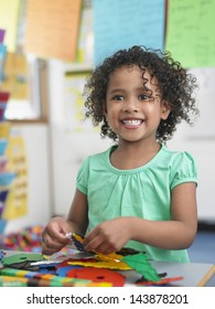 Portrait of smiling little girl assembling  puzzles in classroom
