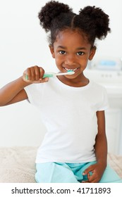 Portrait of a smiling little girl brushing her teeth in the bathroom