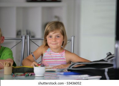 Portrait of a smiling little girl doing homework