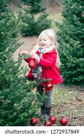 Portrait of smiling little girl hanging baubles on trees. Girl decorating Christmas trees at farm