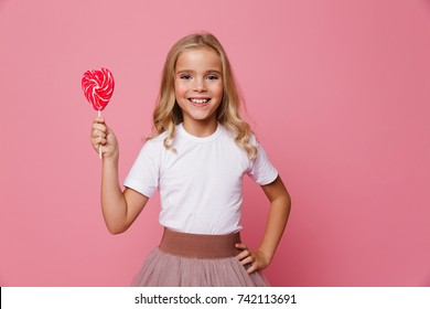 Portrait of a smiling little girl holding heart shaped lollipop isolated over pink background