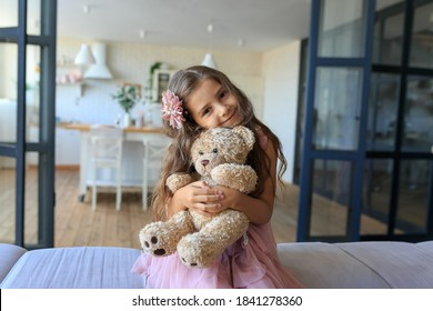 portrait of smiling little girl hugging teddy bear at home. Adorable child with long curly hair with her favorite toy on kitchen background. Happy childhood concept. Cute baby playing with plush bear