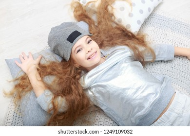 portrait of smiling little girl with long red hair in white christmas decorations