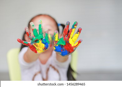 Portrait of smiling little girl looking through her colorful hands and cheek painted in kids room. Focus at baby hands.