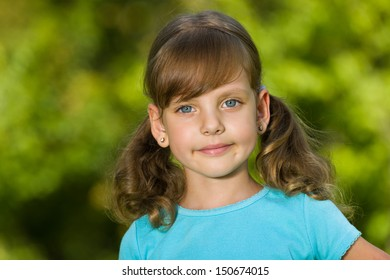 A portrait of a smiling little girl outdoors
