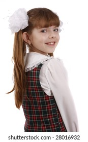 Portrait of smiling, little girl in school uniform. Young pupil is going to school. Isolated on white in studio.