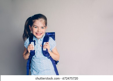 Portrait of smiling, little girl in school uniform with backpack. Isolated on gray.