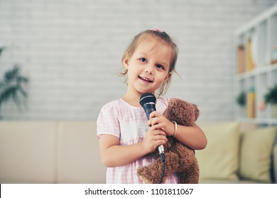 Portrait of smiling little girl singing a song in microphone