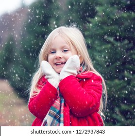 Portrait of smiling little girl standing in snowfall. Cute girl wearing red coat and scarf looking at camera and smiling in winter