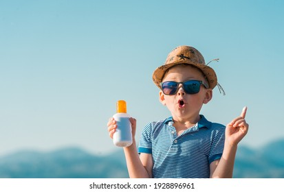 Portrait of smiling little kid boy at tropical beach applying sunblock cream. Child in sunglasses and hat on sunny day. Protection from sunlight. Funny face.