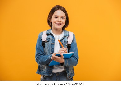 Portrait of a smiling little schoolgirl with backpack holding notebook over yellow background