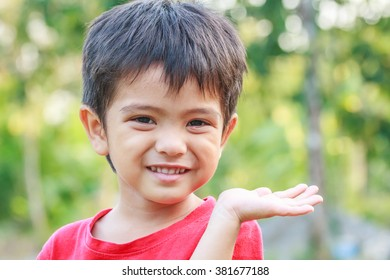 Portrait of smiling little young Asian boy hand palm up in nature