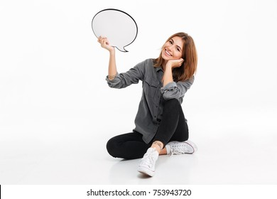 Portrait of a smiling lovely girl holding empty speech bubble while sitting and looking at camera isolated over white background