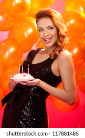 portrait of smiling lovely woman holding cake with candles against balloons