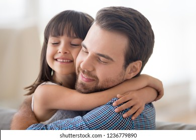 Portrait smiling loving handsome Caucasian father and adorable preschool mixed race daughter indoors. Daddy and child closed eyes embracing sitting on couch at home. Friendly multi-ethnic family