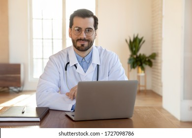 Portrait of smiling male Caucasian doctor wearing whit medical uniform sit at desk in hospital look ta camera posing, happy young man GP or physician work on modern laptop in private clinic