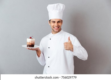 Portrait of a smiling male chef dressed in uniform holding plate with piece of cake and showing thumbs up gesture isolated over gray background