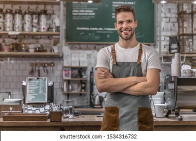 Portrait of smiling male coffee shop owner standing at the counter with look in camera