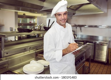 Portrait of a smiling male cook writing on clipboard in the kitchen