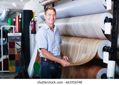 portrait of smiling male customer looking at linoleum flooring in household section