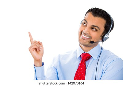 A portrait of a smiling male customer representative pointing at a copy space while talking on a hands free device