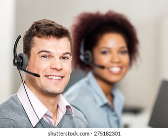 Portrait of smiling male customer service representative with female colleague working in office