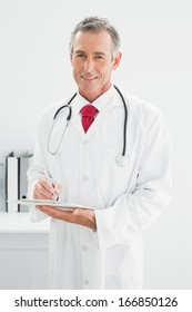 Portrait of a smiling male doctor writing a report at the medical office