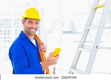 Portrait of smiling male electrician holding multimeter in bright office