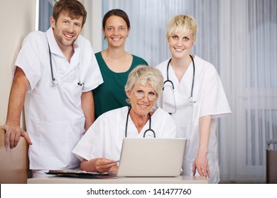 Portrait of smiling male and female doctors with laptop at desk in hospital