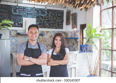 Portrait of smiling male and female waitress standing with arms crossed in cafe