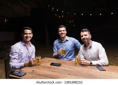 Portrait of smiling male friends having beer while sitting at dining table in backyard