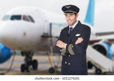 Portrait Of A Smiling Male Pilot With Folded Hands In Front Of Airplane