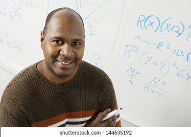 Portrait of a smiling male professor in front of whiteboard with equations