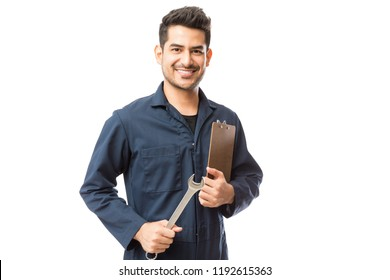 Portrait of smiling male repairman holding wrench and clipboard over white background