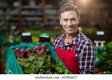 Portrait of smiling male staff holding a crate of fresh vegetables at supermarket