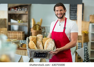 Portrait of smiling male staff holding a basket of baguettes at counter in bake shop