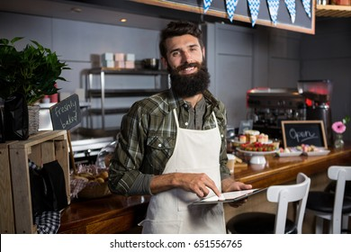 Portrait of smiling male staff using digital tablet at counter in coffee shop